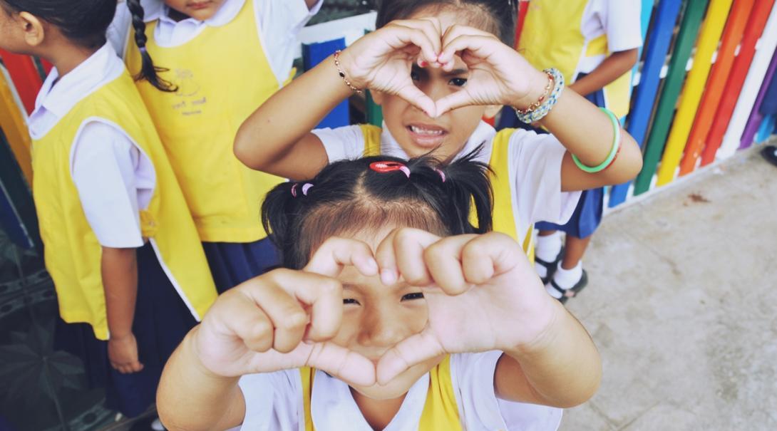 手でハートの形を作るアジアの子供たちの写真